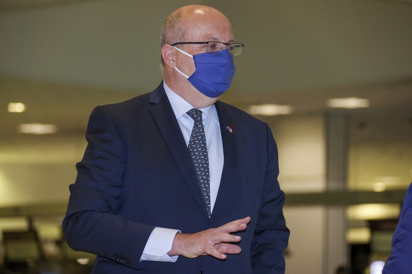 """France's Ambassador to Australia Jean-Pierre Thebault gestures as he arrives at Sydney Airport, Saturday, Sept. 18, 2021. Thebault has described as a """"huge mistake"""" Australia's surprise cancellation of a major submarine contract in favor of a U.S. deal, in an unprecedented show of anger among the allies. (AP Photo/David Gray)"""