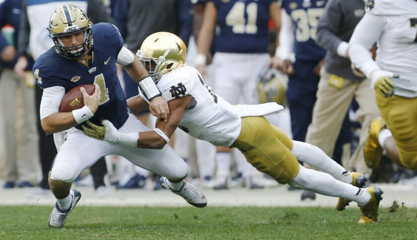 Pittsburgh quarterback Nathan Peterman (4) is tackled by Notre Dame safety Max Redfield (10) after scrambling for a first down in the third quarter of an NCAA football game, Saturday, Nov. 7, 2015 in Pittsburgh. Notre Dame won 42-30. (AP Photo/Keith Srakocic)
