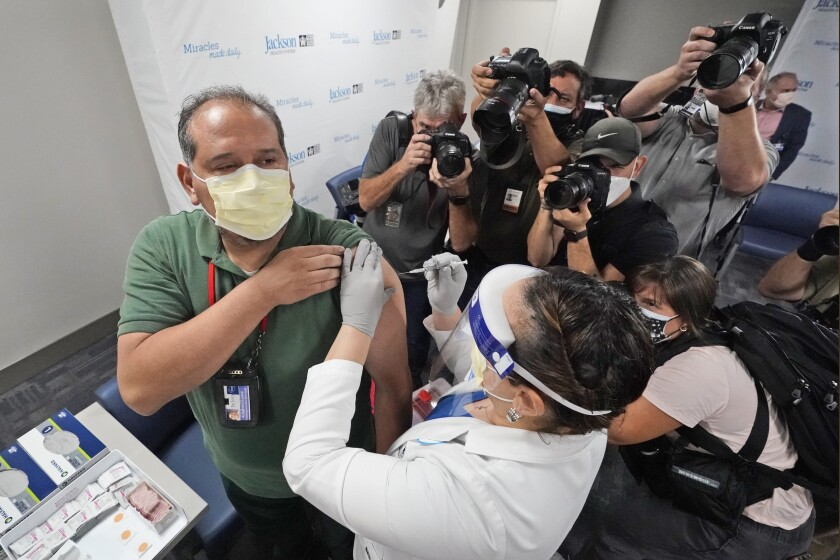 Surrounded by photographers, Armando Acosta, left, an environmental service worker at Jackson Memorial Hospital, prepares to be inoculated with the Pfizer-BioNTech COVID-19 vaccine, Tuesday, Dec. 15, 2020, at Jackson Memorial Hospital in Miami. (AP Photo/Wilfredo Lee)