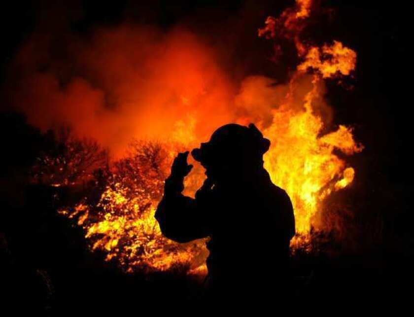 "A firefighter surveys a scene at the 2003 Cedar fire in San Diego County, a blaze that was a ""game changer"" for mutual-aid firefighting in California."