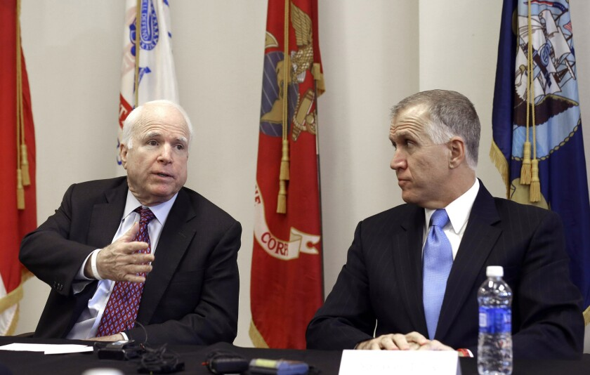 Sen. John McCain (R-Ariz.) and North Carolina Senate candidate Thom Tillis participate in a national security roundtable in Goldsboro, N.C., on Thursday. Tillis was one of the first Republicans to suggest banning travel to the United States from West African nations dealing with the Ebola outbreak.