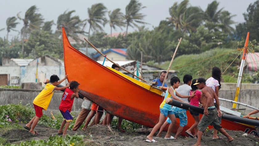 Filipinos secure a boat in the town of Aparri, Cagayan province, Friday as Typhoon Mangkhut bears down.
