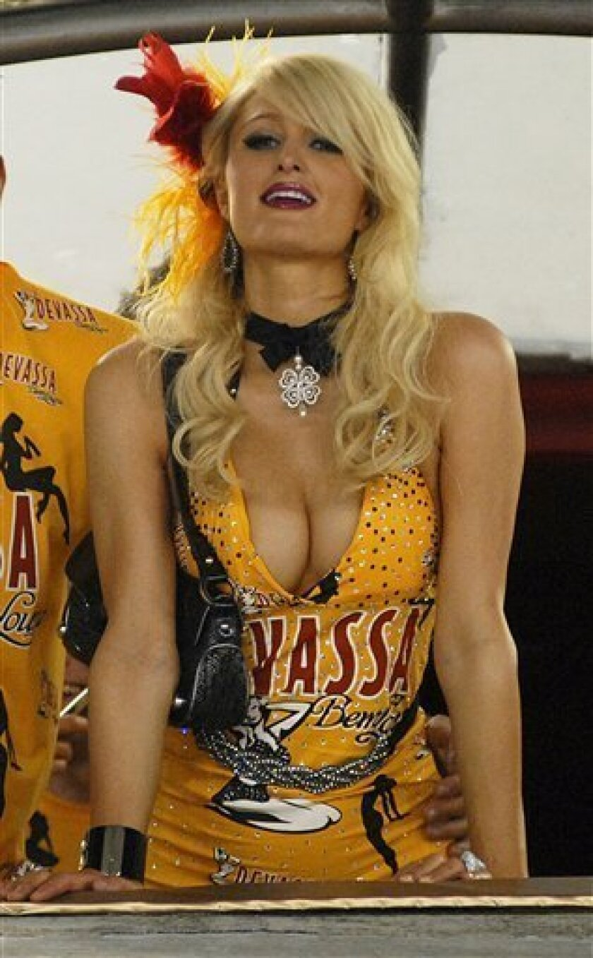 In this photo taken Feb. 14, 2010, U.S. actress and socialite Paris Hilton watch a carnival parade at the Sambadrome, in Rio de Janeiro. A sultry beer ad featuring the socialite has been pulled after consumer complaints and a watchdog agency's investigation.The television and Internet ad featured Hilton in a short black dress preening and rubbing a can of Devassa beer on herself, all to the delight of onlookers watching through her window. (AP Photo/Renzo Gostoli)