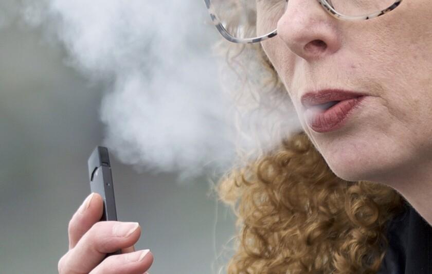 Vaping from a Juul pen e-cigarette