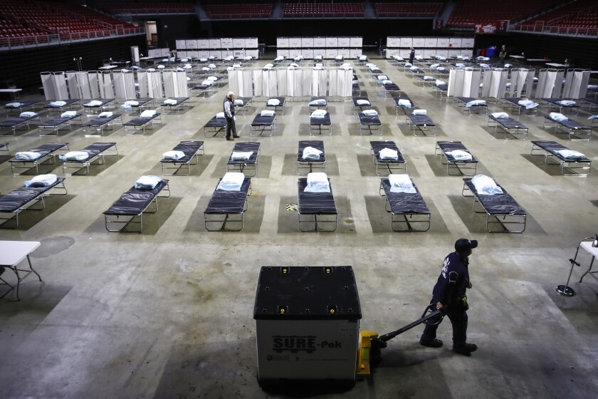 A worker pulls a pallet of supplies past rows of cots set up in a large, open building.