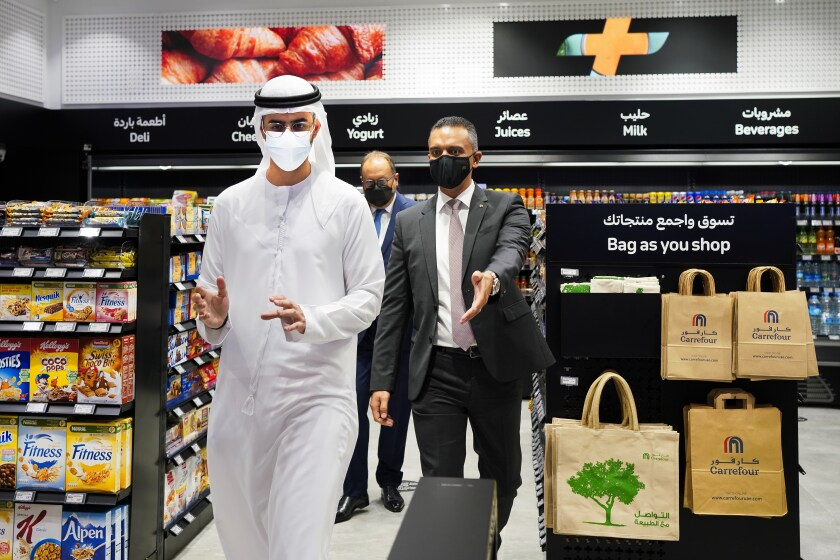 From left, Emirati Minister of State for Artificial Intelligence Omar Sultan al-Olama, Majid Al Futtaim CEO Alain Bejjani and Majid Al Futtaim Retail CEO Hani Weiss leave Carrefour's new cashier-less grocery store in Mall of the Emirates in Dubai, United Arab Emirates, Monday, Sept. 6, 2021. The Middle East on Monday got its first completely automated cashier-less store, as retail giant Carrefour rolled out its vision for the future of the industry in a cavernous Dubai mall. (AP Photo/Isabel DeBre)