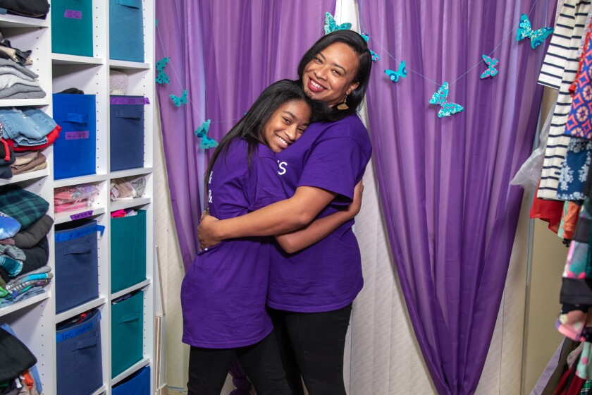 Sharia Linton, 12, and her mother, Shamine Linton, embrace and smile at the camera while standing in their nonprofit office