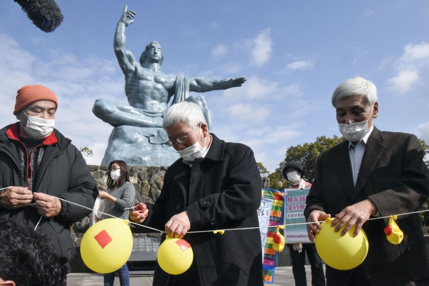 People deflate balloons in symbolic hope of demolishing nuclear warheads at a gathering in Nagasaki, Japan, on Friday.