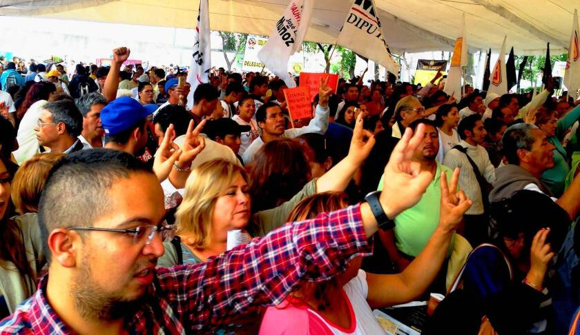 """Emmanuel Martinez, foreground, left, a 25-year-old government worker, sings the Mexican national anthem along with a crowd of hundreds to close a rally against opening the national oil company, Pemex, to foreign investment. """"Oil is a treasure that belongs to the Mexican people,"""" Martinez said."""