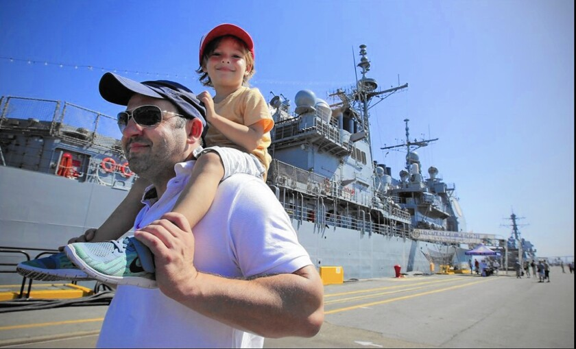 Daimhin Murphy, carrying his son Gavin, walks past the Cape St. George, one of three ships open for public tours during the 2015 Fleet Week San Diego.