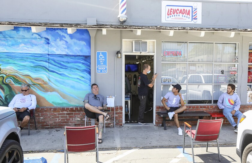 Socially distanced customer sit outside of the Leucadia Barber Shop on May 27, 2020 in Encinitas, California. This was the first day salons have been allowed to reopen since the shutdown.