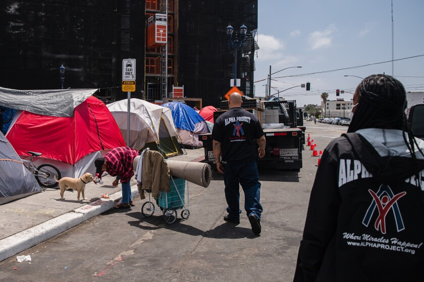 Outreach specialists talk with homeless people in downtown San Diego.
