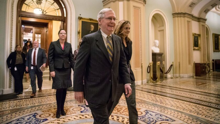 After speaking on the floor, Senate Majority Leader Mitch McConnell, R-Ky., leaves the chamber as a bitterly-divided Congress hurtles toward a government shutdown at the Capitol in Washington, Friday, Jan. 19, 2018.