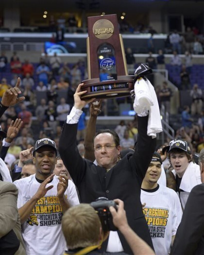 Wichita State coach Gregg Marshall holds the regional trophy as he poses with his players after they defeated Ohio State 70-66 in the West Regional final in the NCAA men's college basketball tournament, Saturday, March 30, 2013, in Los Angeles. (AP Photo/Mark J. Terrill)