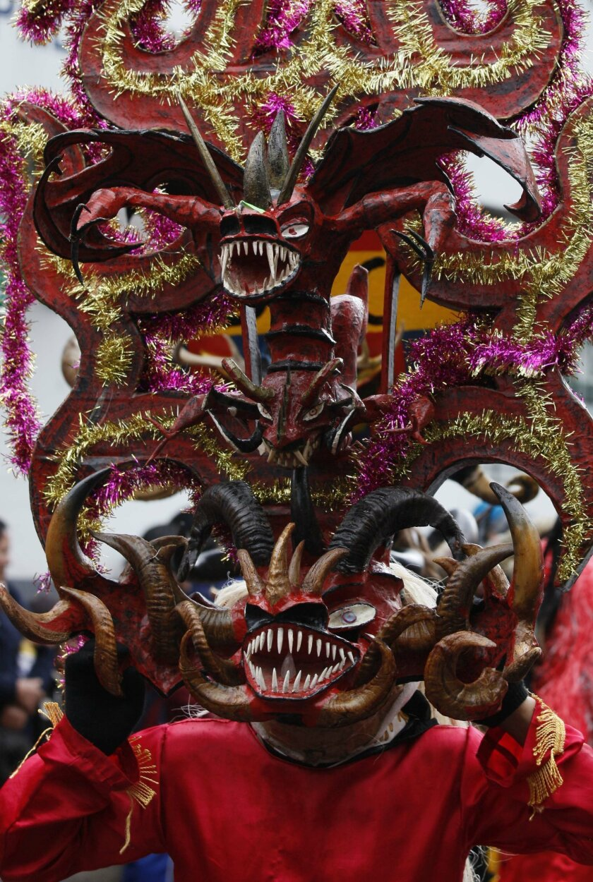 A man with a devil's mask dances in La Diablada in Pillaro, Ecuador, Monday, Jan. 6, 2014, to celebrate the end of the year and the start of the new one. The town of Pillaro kicks off the feast of La Diablada with neighborhoods competing to bring in as many people as possible dressed as different c