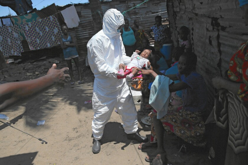 A health worker carries an infant to an Ebola treatment unit in Monrovia, Liberia. Officials say the Ebola outbreak has sickened nearly 20,000 and killed about 7,700 of them.