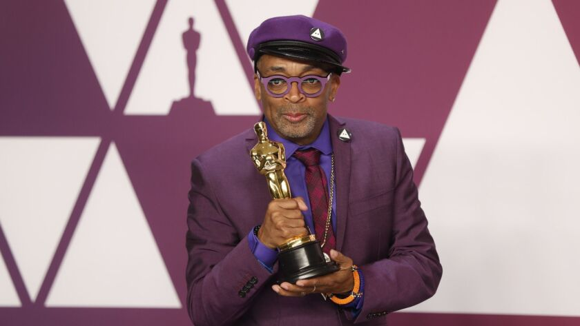 "Spike Lee holds his Oscar for adapted screenplay for ""BlacKkKlansman."""