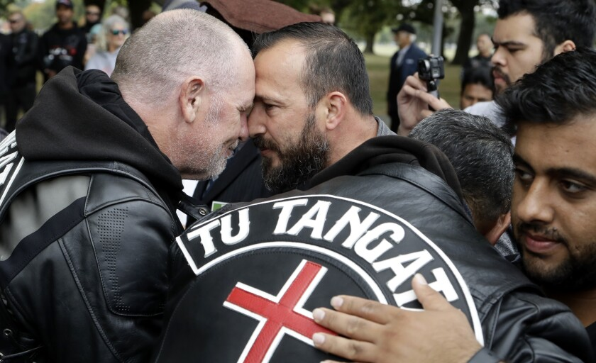 Survivor of the Al Noor mosque shootings, Temel Atacocugu, center, exchanges a hongi with a member of the Tu Tangata motorcycle club outside the mosque in Christchurch, New Zealand, Sunday, March 15, 2020. A national memorial in New Zealand to commemorate the 51 people who were killed when a gunman attacked two mosques one year ago has been canceled due to fears over the new coronavirus. (AP Photo/Mark Baker)