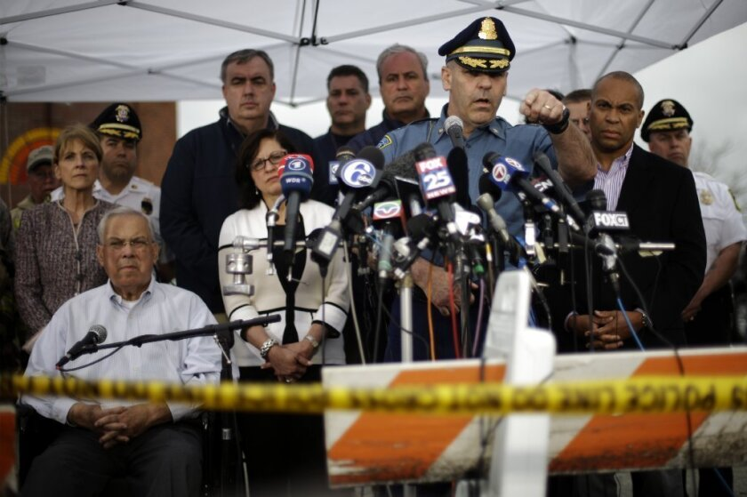 Massachusetts State Police Col. Timothy Alben, at microphones, accompanied by Gov. Deval Patrick (in sport coat) and other officials, met with the news media as Friday's manhunt dragged on in Boston.