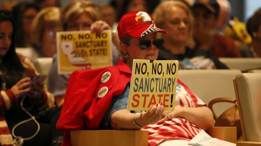 """Opponents of California's Senate Bill 54, a key """"sanctuary state"""" law, display signs during a Newport Beach City Council meeting Tuesday night."""