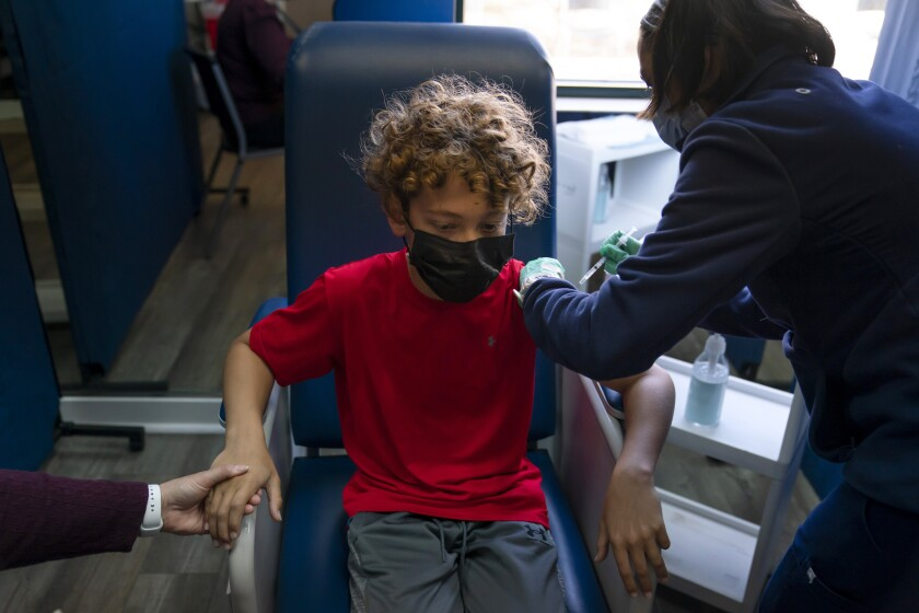 A 12-year-old holds his mother's hand as he receives a COVID-19 vaccine