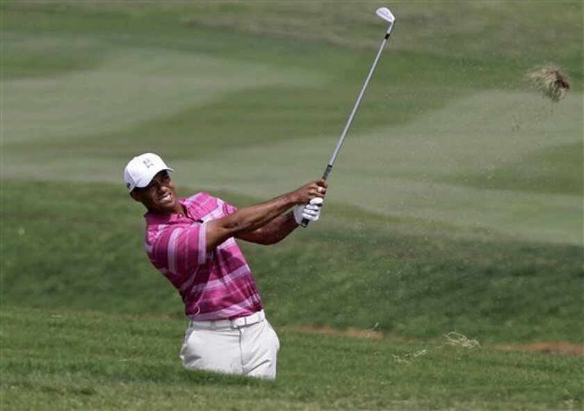 Tiger Woods of the United States hits the ball from a bunker of the first hole during the Skins Games charity golf tournament, marking King Bhumibol's 60th year on the Thai throne, on the Amata Spring Country Club course in Chonburi province, southeastern Thailand, Monday, Nov . 8, 2010. (AP Photo/Sakchai Lalit)
