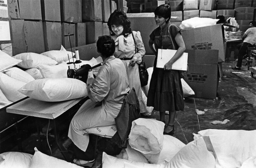 Cristina Ramirez, center, an organizer for the International Ladies Garment Workers Union, visits workers at a factory.