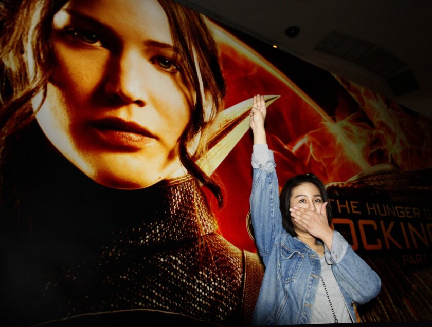 "Nachacha Kongudom, 21, raises a three-finger salute outside a Bangkok cinema where ""The Hunger Games: Mockingjay - Part 1"" was shown Nov. 20."
