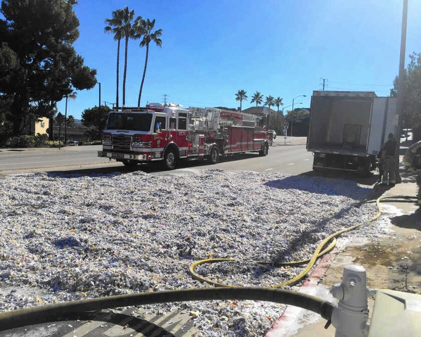 Newport Beach firefighters dumped about 5,000 pounds of paper out of a document shredding truck Tuesday so they could douse a fire that broke out in the cargo area.