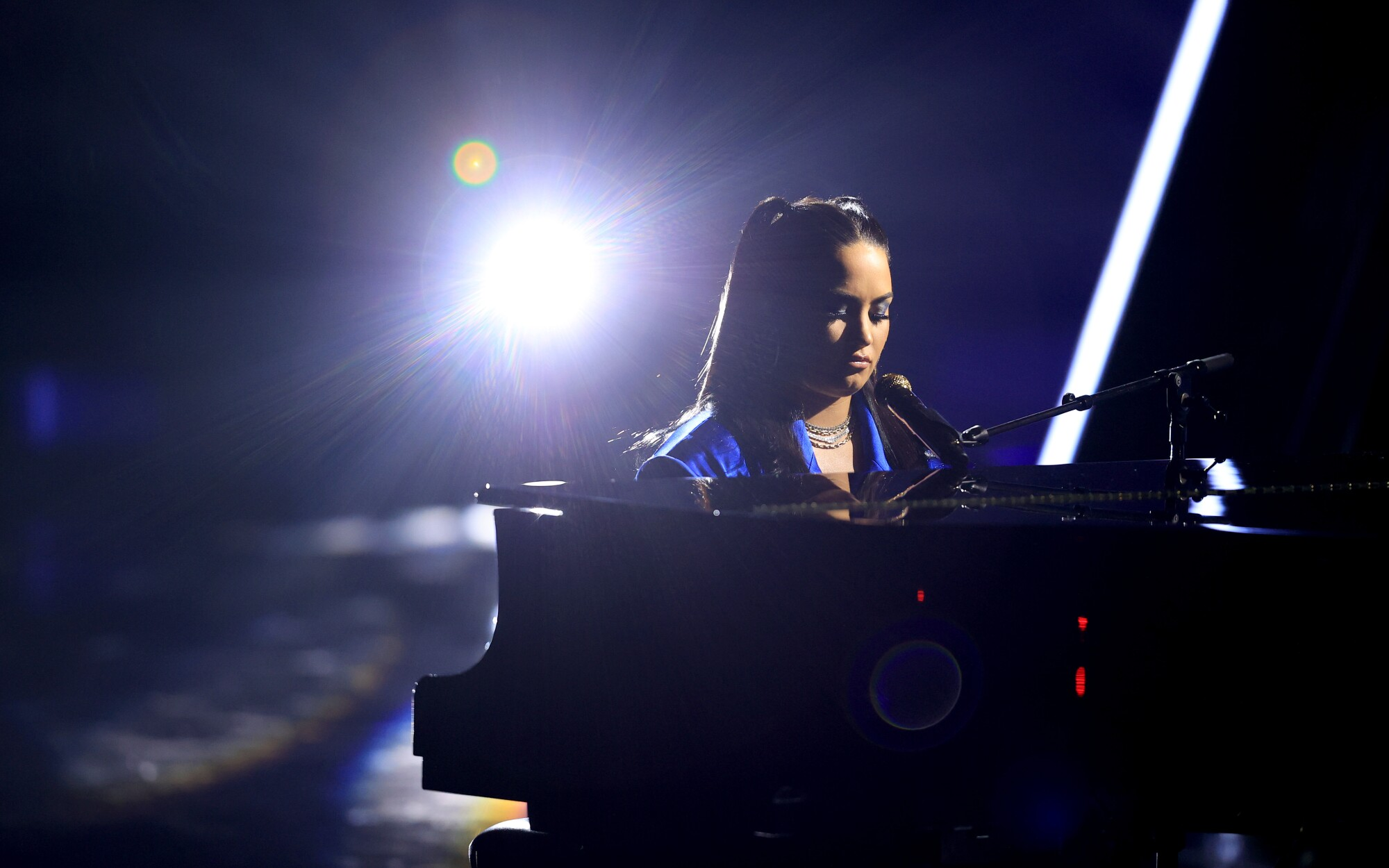 Demi Lovato sits at a grand piano as she performs at the 2020 Billboard Music Awards.