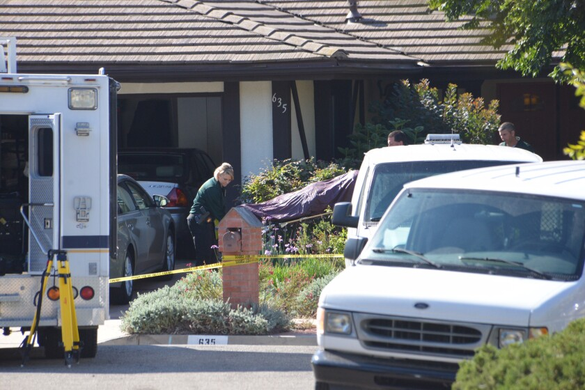 Investigators remove a body from a Santa Barbara County home where four people were found stabbed to death.