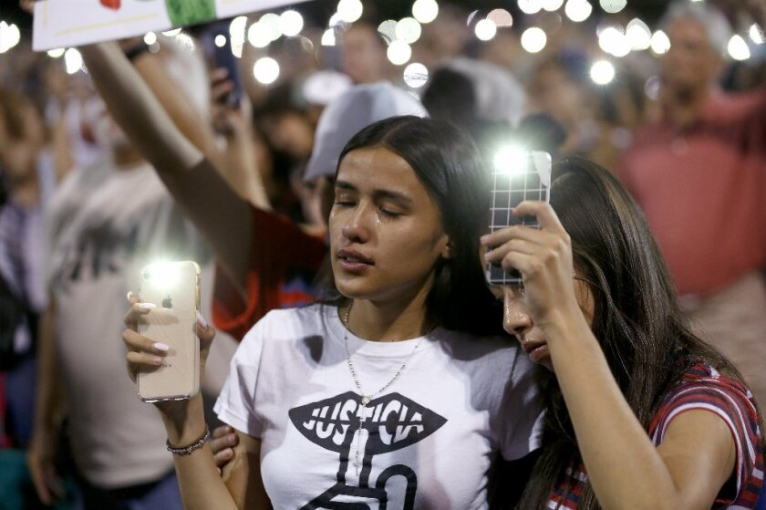 Samantha Salazar, left, and Sarah Estrada join mourners gathered at Ponder Park in El Paso, Texas for a community vigil on Sunday night, Aug. 4, 2019, after a mass shooting at a Walmart the day before.