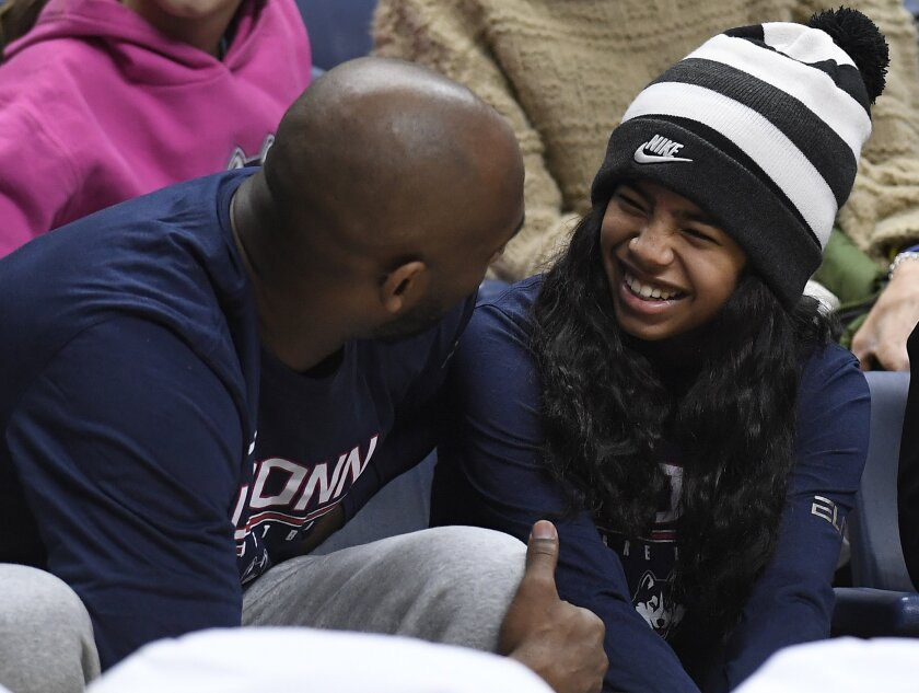 Kobe Bryant and his daughter Gianna watch the first half of an NCAA college basketball game between Connecticut and Houston.
