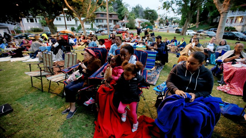 """Families settle in for a twilight showing of the movie """"The Wiz"""" in the View Park neighborhood on June 13, 2015."""