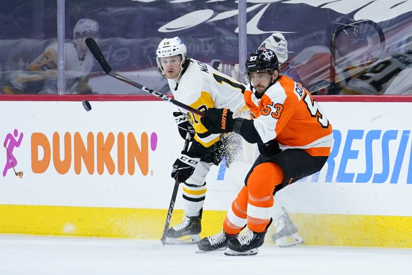 Philadelphia Flyers' Shayne Gostisbehere, right, and Pittsburgh Penguins' Jared McCann battle for the puck during the second period of an NHL hockey game, Tuesday, May 4, 2021, in Philadelphia. (AP Photo/Matt Slocum)