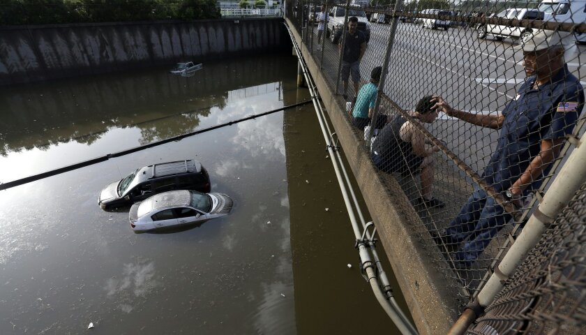 FILE - In this May 29, 2015 file photo, cars sit in floodwaters along Interstate 45 after heavy overnight rain flooded parts of the highway in Houston. Even for a world getting used to wild weather, May seems stuck on strange. Torrential downpours in Texas, whiplashing the region from drought to flooding. A heatwave that has already killed more than 1800 in India and is the fifth deadliest since 1900. Record 91 degree temperature in of all places Alaska. A pair of top-of-the-scale typhoons in the Northwest Pacific. And a drought in the U.S. East is starting to take root just as the one ends in Texas. (AP Photo/David J. Phillip, File)
