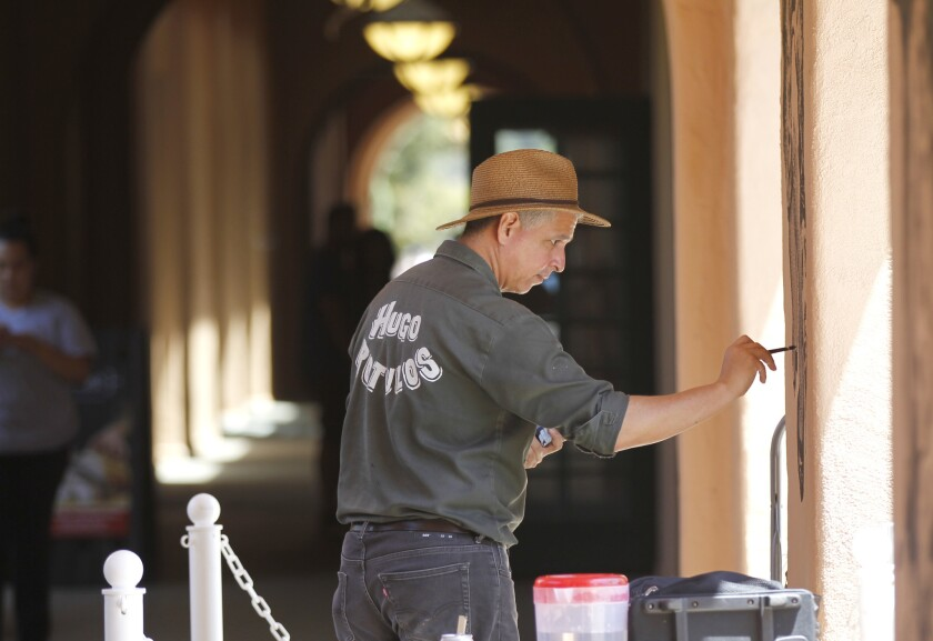 "Tijuana artist Hugo Crosthwaite paints live in front of guests at the Instillations at the Station art event at the Arts District of Liberty Station in San Diego on Aug. 5, 2018. Crosthwaite's live paintings ""Column A and Column B: A Continual Mural Narrative Performance"" will run through Aug. 17."