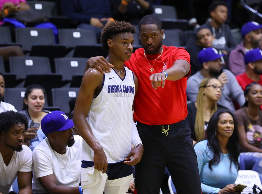 Dwyane Wade puts his arm around Sierra Canyon's Bronny James on Saturday at halftime of a fall tournament game at Cal State Los Angeles.