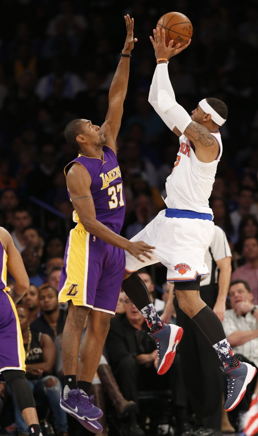 New York Knicks forward Carmelo Anthony (7) shoots over Los Angeles Lakers forward Metta World Peace (37) in the first half of an NBA basketball game at Madison Square Garden in New York, Sunday, Nov. 8, 2015. (AP Photo/Kathy Willens)
