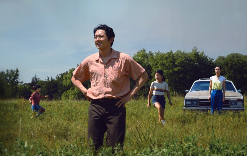 "Steven Yeun stands in a field with his movie family in a scene from ""Minari."""