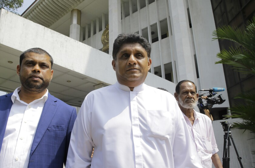 FILE- In this Nov. 12, 2018 file photo, Sri Lankan lawmaker Sajith Premadasa, center, leaves the supreme courts complex after attending a filing in of a petition in Colombo, Sri Lanka. Sri Lanka's governing coalition has named its charismatic deputy leader, Premadasa, as its candidate for in November's presidential election, ending a long tussle with the party leader, Prime Minister Ranil Wickremesinghe, over the nomination. (AP Photo/Eranga Jayawardena, File)