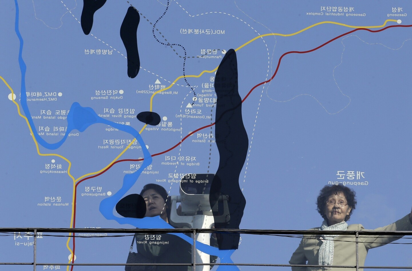 Visitors look toward North Korea through a map of the area around the demilitarized zone near the border village of Panmunjom.
