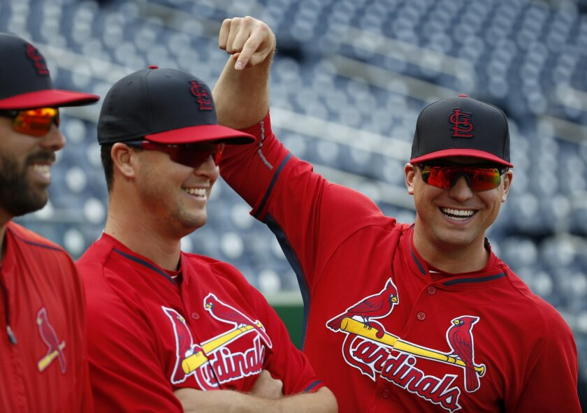 St. Louis Cardinals pitcher Mitch Harris, second left, a 29-year-old graduate of the U.S. Naval Academy, smiles as fellow relief pitcher Trevor Rosenthal, right, points him out for the media during batting practice before a baseball game against the Washington Nationals at Nationals Park, Tuesday, April 21, 2015, in Washington. Harris was called up from Triple-A Memphis on Tuesday. (AP Photo/Alex Brandon)