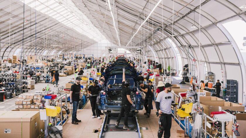 Employees work on the Tesla Model 3 assembly line in Fremont, Calif., June 28.