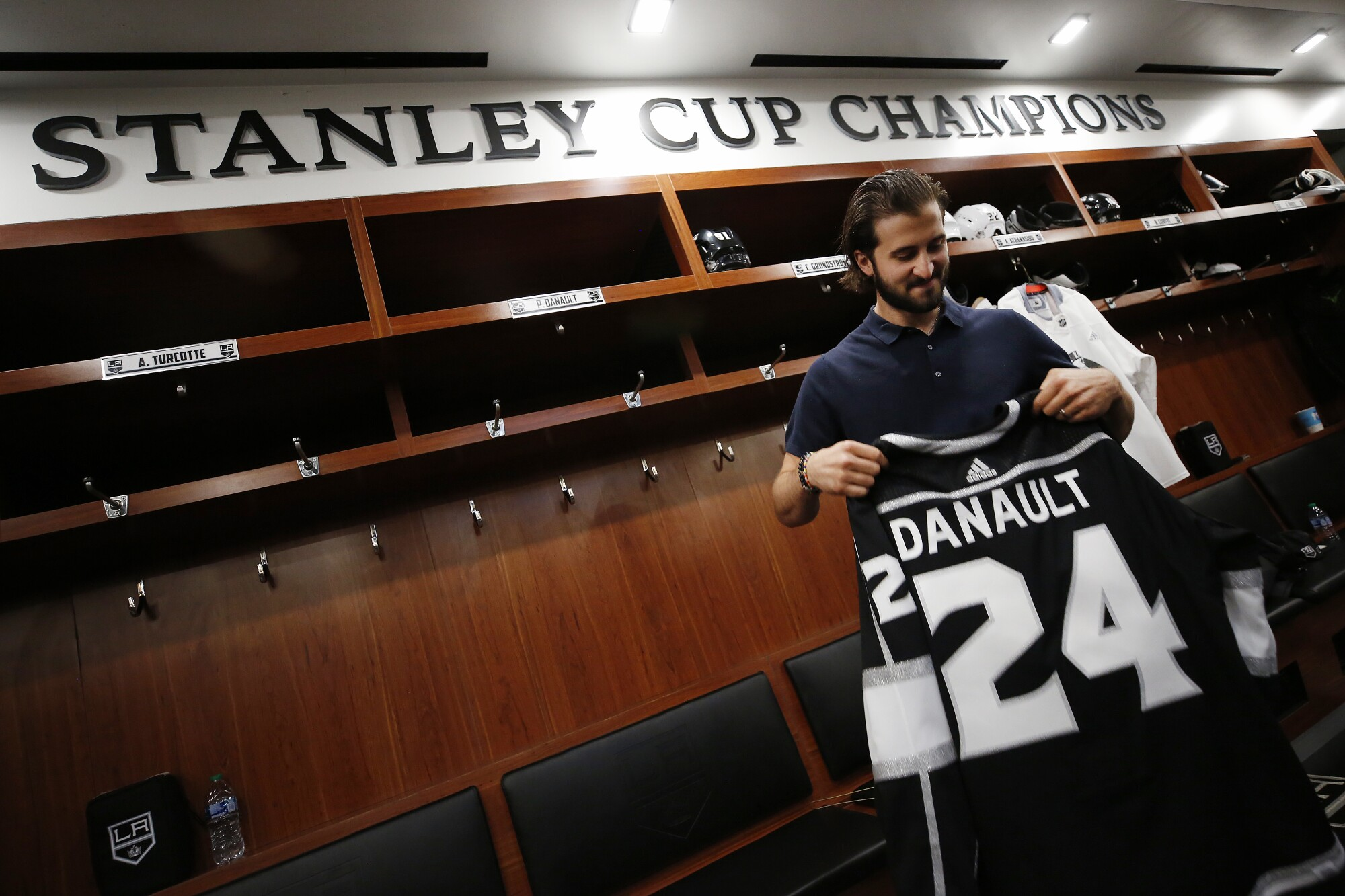 Los Angeles Kings player Phillip Danault holds his team jersey in the locker room of the L.A. Kings practice facility