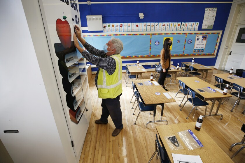 A man in a neon vest works in a classroom