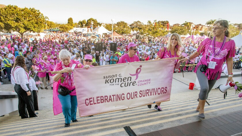Participants and organizers mount the steps of the Pacific Life building during the 2016 Susan G. Komen Race for the Cure in Newport Beach. The event, now called the More than Pink Walk, returns Sunday.