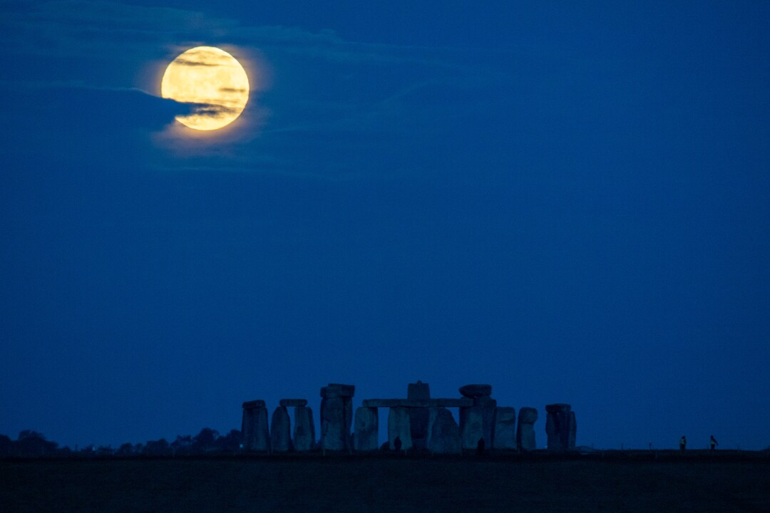 La luna sanguinolenta del super fiore tramonta sulla sagoma delle pietre di Stonehenge