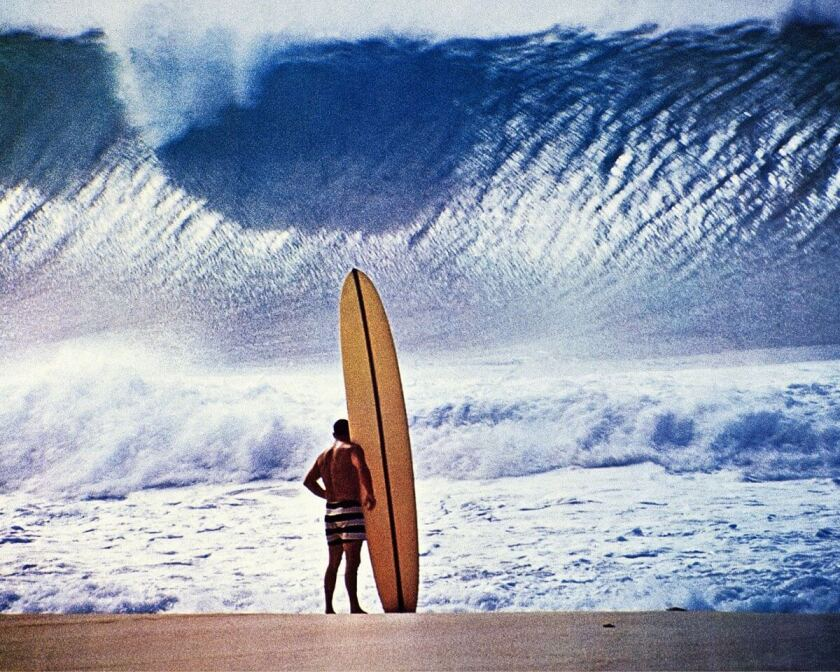 A man with a longboard faces a giant wave on a beach.