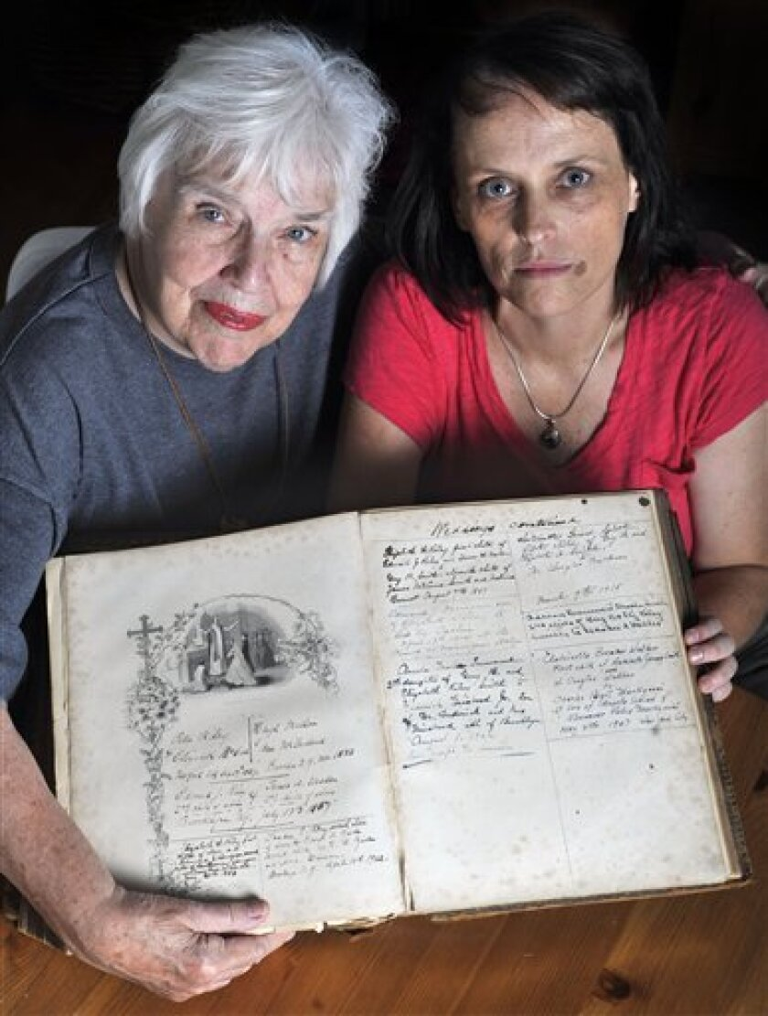 Antoinette Martignoni, left, and her granddaughter Greta Blau hold a family Bible that contains the name of their ancestor, Dr. James McCune Smith, the nation's first African American physician at Martignoni's home in Fairfield, Conn., Thursday, Sept. 23, 2010. (AP Photo/Jessica Hill)